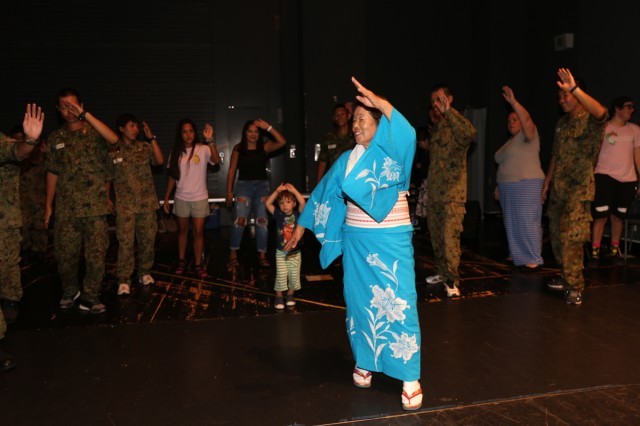 Masako Kawasaki, a volunteer instructor from the Zama City Women's association, teaches members of the U.S. Army Garrison Japan community a traditional Japanese dance July 19, 2018, in the Camp Zama's Community Recreation Center to prepare them for the Garrison's Aug. 4 Bon Odori open house festival. (U.S. Army photos by Noriko Kudo)