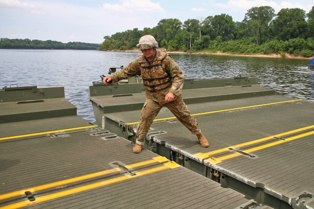 Pvt. Jeremy Smith with the 2061st Multi-Role Bridge Company helps guide two interior bridge bays together during River Assault 2018 on the Arkansas River near Fort Smith, Ark., July 24, 2018. The Kentucky Guardsmen participated with Army Reserve, active duty Army and Marine Corps units for the annual engineer exercise.