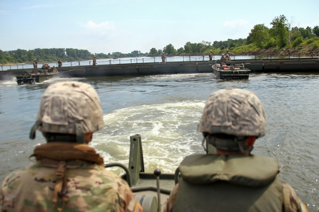 Soldiers with the 2061st Multi-Role Bridge Company steer their boat away from bridge construction during River Assault 2018 on the Arkansas River near Fort Smith, Ark., July 25, 2018. The Kentucky Guardsmen participated with Army Reserve, active duty Army and Marine Corps units for the annual engineer exercise.