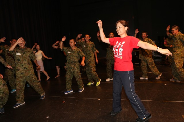 Mikako Ohno, Public Affairs Specialist, a liaison for the event, shows the members of Camp Zama community a traditional Japanese dance's move July 19, 2018, in the Camp Zama's Community Recreation Center. (U.S. Army photo by Noriko Kudo)