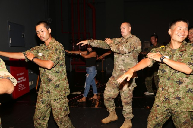 Capt. Patrick Sorensen, center, assigned to U.S. Army Japan, practices a traditional Japanese dance along with JGSDF members July 19, 2018, in the Camp Zama's Community Recreation Center to get ready for the Garrison's Aug. 4 Bon Odori open house festival. (U.S. Army photo by Noriko Kudo)