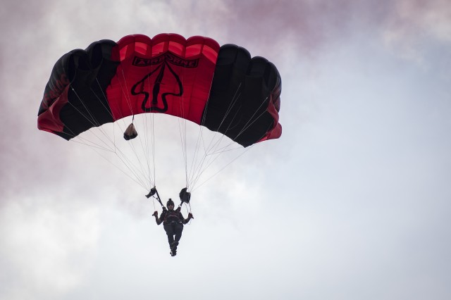 A U.S. Army Special Operations Command Black Daggers Parachute Demonstration Team member parachutes down to the drop zone during the Fort Eustis 100th Anniversary Open House at Joint Base Langley-Eustis, Va., July 28, 2018. The team's mission is to perform live aerial demonstrations in support of Army Special Operations community relations and recruiting.