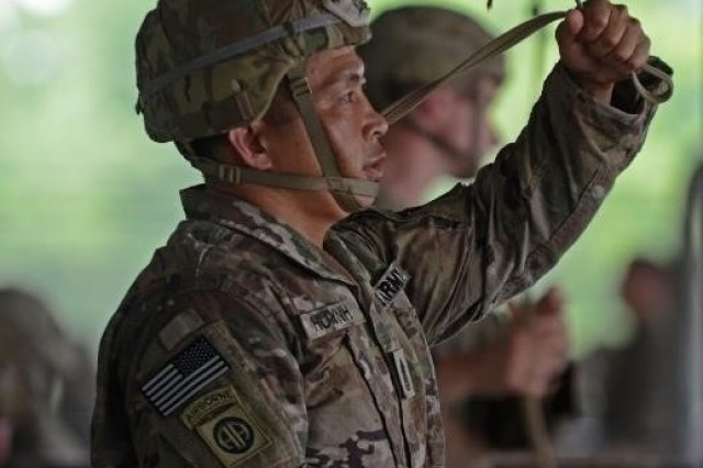 Command Sgt. Maj. Thinh Huynh, the senior enlisted advisor of 1st Battalion, 504th Parachute Infantry Regiment, 1st Infantry Brigade Combat Team, 82nd Airborne Division, holds a static line while conducting pre-jump training during Operation Devil Storm at Green Ramp, Fort Bragg, N.C., July 17, 2018.