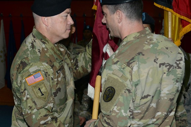 Army Col. Timothy Hudson (right), commander of Landstuhl Regional Medical Center, passes the LRMC colors to the incoming command sergeant major, Command Sgt. Maj. Thurman Reynolds during his assumption of responsibility ceremony on Aug. 1. The passing of the colors from the commander to the command sergeant major symbolizes the faith and trust that a commander places in his top senior enlisted advisor to lead the unit.