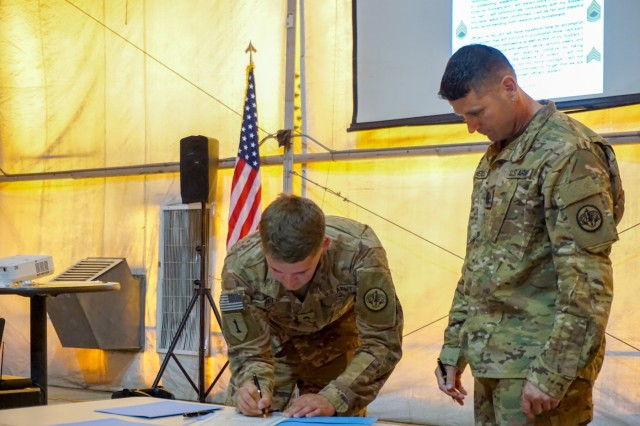 "Command Sgt. Maj. Kim Mendez, 1st Squadron, 3rd Cavalry Regiment ""Brave Rifles,"" command sergeant major, observes as a new non-commissioned officer signs the Charge to the NCO during an NCO induction ceremony in Iraq August 3, 2018. Brave Rifles troopers are deployed to Iraq in support of Combined Joint Task Force Operation Inherent Resolve, working by, with and through the Iraqi Security Forces and coalition partners to defeat ISIS in Iraq and Syria."