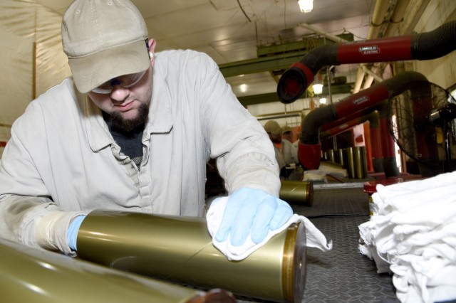 Matt Kuykendall, an Industrial Operations Division employee at McAlester Army Ammunition Plant, Okla., wipes clean the inside of a just grinded 105mm artillery case to prepare it for painting, which is the final step in the case renovation process. The cases are then sent to another building on the installation where they are loaded, assembled and packed as if they were new. The Lean Six Sigma case renovation project is expected to produce approximately $1,878,463 in cost savings benefits over seven years.