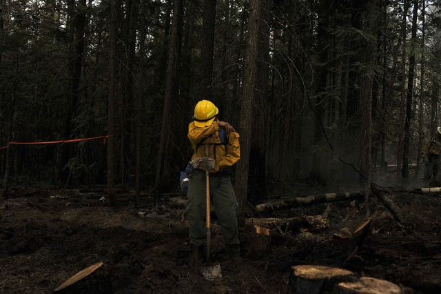 A Washington Army National Guard Soldier takes a moment to wipe sweat from his face as he fights a wild fire near Northport, Wash., Aug. 5, 2018.
