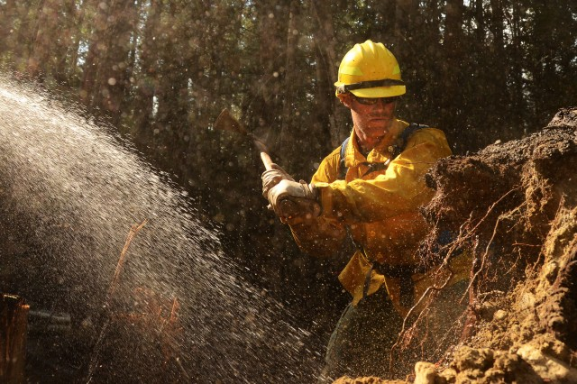 "Washington Air National Guard Master Sgt. Luke Anderson, 141st Communications Squadron ""mops up"" an area of the Sheep Creek fire Aug. 6, 2018, near Northport, Wash."