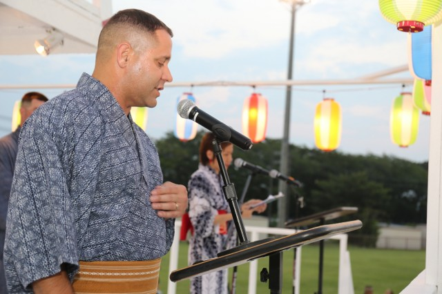 """Col. Phillip K. Gage, commander of USAG Japan, clad in a traditional Japanese summer kimono known as """"yukata,"""" welcomes event attendees during the 59th annual Bon Odori Festival held Aug. 4, 2018, on Camp Zama, Japan. More than 20,000 Japanese and American community members attended the festival, which had dancing, live entertainment, food, and games. (U.S. Army photo by Noriko Kudo)"""