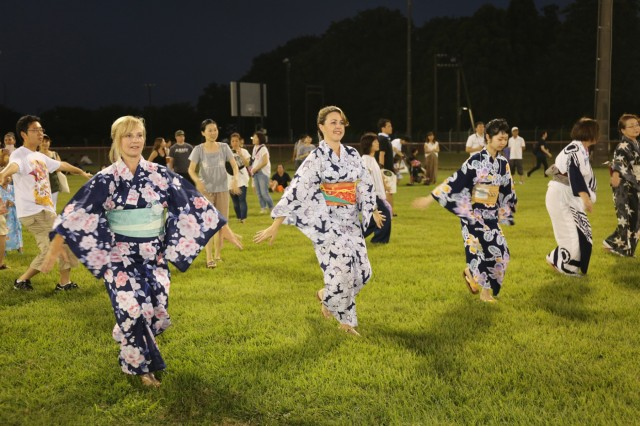 Community members perform the moves of a traditional Japanese dance on Camp Zama, Japan, during the 59th annual Bon Odori Festival, Aug. 4, 2018. More than 20,000 people attended the festival, which had dancing, live entertainment, food, and games.  (U.S. Army photo by Noriko Kudo)