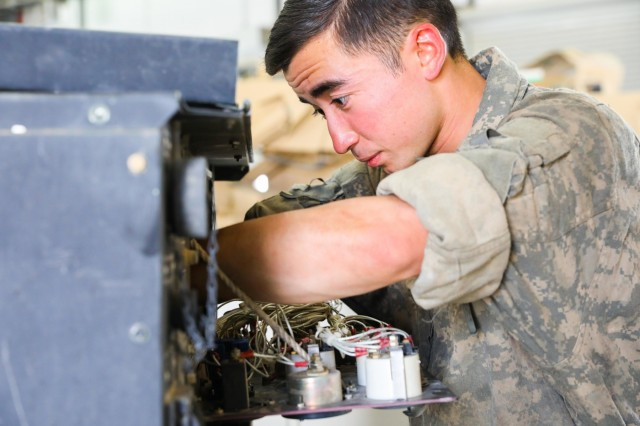 KANDAHAR PROVINCE, Afghanistan (Aug. 2, 2018) -- U.S. Army Spc. Ian R. Adams, a generator mechanic assigned to Golf Company, 1st Battalion, 12th Infantry Regiment, 2nd Infantry Brigade Combat Team, 4th Infantry Division, conducts preventive maintenance checks and services on a generator, Aug. 2, 2018,  at the company's motor pool area in Kandahar Airfield, Afghanistan.  Adams, a native of Okinawa, Japan, services generators for all U.S. and NATO service members on the airfield. (U.S. Army photo by Staff Sgt. Neysa Canfield/2nd Infantry Brigade Combat Team Public Affairs)