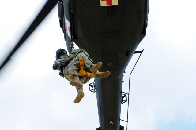 A Soldier with Detachment 1, Charlie Company, 2nd Battalion 238th Aviation Regiment, secures a simulated patient as they are raised to a UH-60 Black Hawk during medical air evacuation training near Morehead, Ky., July 26, 2018.