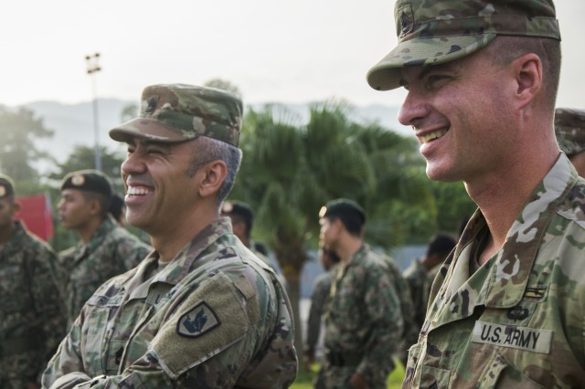 Sgt. 1st Class Omar Trujillo, Headquarters and Headquarters Detachment, 96th Troop Command, and Staff Sgt. Scott Salmon, 540th Chemical Detachment, 420th Chemical Battalion, 96th Troop Command, Washington Army National Guard, wait for the closing ceremony of Exercise Keris Strike 2018 to begin, Aug. 3, 2018. Keris Strike 2018 is a bilateral exercise between the U.S. and Malaysia that focuses on humanitarian disaster relief efforts.
