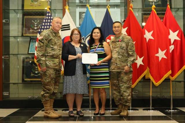Kimberly S Luong, spouse of Maj. Gen. Viet X. Luong, is awarded the Outstanding Civilian Service Medal for her service to the Soldiers, civilians and family members of Eighth Army at Eighth Army Headquarters, U.S. Army Garrison Humphreys, Aug. 8. Luong will soon take over as the new incoming commanding general for U.S. Army Japan (USARJ) after the dedication that he and his wife gave to Eighth Army since July 2017.