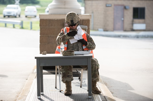 A Soldier checks names on the list to determine who is allowed access on post during the exercise.