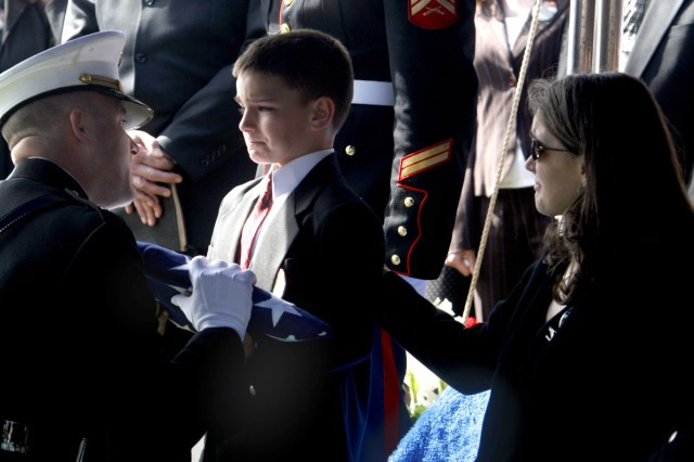 Christian Golczynski stands to receive the flag at his father Marine Staff Sgt. Marc Golczynski's funeral in 2007.