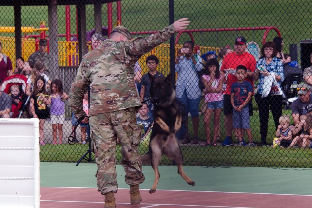 A trainer works with one of Fort Jackson's military working dogs during the National Night Out military working dog demonstration. He shows off some of the dog's skills.