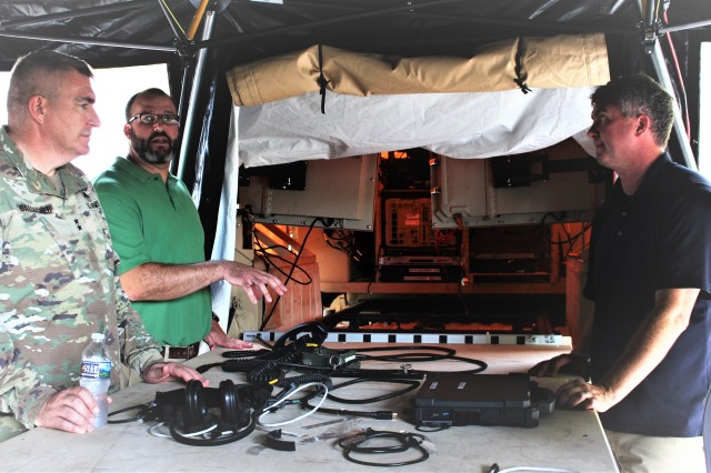 Tyler Barton, EMC STO-D Manager, center, and Brad McNeilly-Anta, Command Post consultant, right, demonstrate to Maj. General Pete Gallagher, the U.S. Army's Network Cross Functional Team Director, how the Light-Mobile Command Post's quick erect table and large screen displays are key time saving capabilities when setting up and tearing down the command post.
