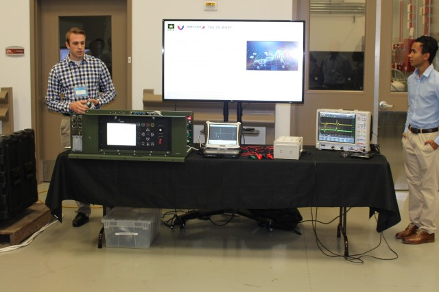Joe Vitale, left, and Blane Wilson, U.S. Army Communications-Electronics Center electrical engineers, demonstrate the Energy Informed Operations software application, which works through an intelligent microgrid to allow Soldiers to interactively monitor and manage power systems.