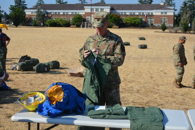 Lt. Col. Eric Parthemore, the 14th Brigade Engineer Battalion commander, is issued a pair of firefighting protective pants during the initial stages of preparation to support the National Interagency Fire Center in suppressing the wildfires in the Western United States, Aug. 9, 2018, Joint Base Lewis McChord. (U.S. Army photo by Staff Sgt. Kenneth Pawlak, 2nd Stryker Brigade Combat Team)