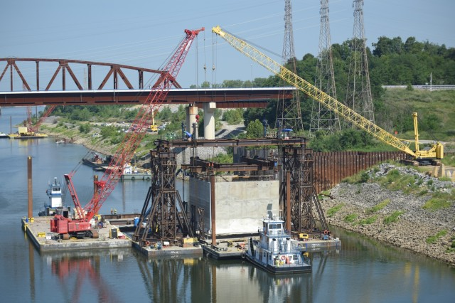 A tow boat pulls out a barge after a gantry crane picked up a 1.3 million pound concrete shell Aug. 3, 2018 downstream of Kentucky Lock in Grand Rivers, Ky. The U.S. Army Corps of Engineers Nashville District and contractor, Johnson Brothers, were preparing to place it on the riverbed where it will be part of a coffer dam and eventually a permanent part of the new lock wall for the Kentucky Lock Addition Project. An issue with the strand jack delayed the placement of the concrete shell until Aug. 6. It is the first of 10 shells being placed over the next year. The lock is located at Kentucky Dam, which is a Tennessee Valley Authority project at Tennessee River mile 22.4. (USACE Photo by Leon Roberts)