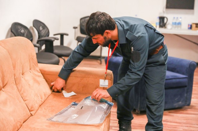 KANDAHAR AIRFIELD, Afghanistan (July 17, 2018) -- An officer from the Afghan National Police collects simulated evidence, July 17, 2018, during a practical exercise for an interview and reporting course in Kandahar Airfield, Afghanistan. The course is taught to officers from the Afghan National Police by members of the Police Advisory Team for Train, Advise and Assist Command-South to help enable the Afghan National Defense and Security Forces combat capabilities. (U.S. Army photo by Staff Sgt. Neysa Canfield)