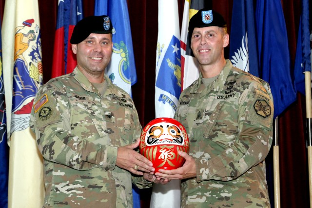 Command Sgt. Maj. Billy J. Norman, U.S. Army Garrison Japan command sergeant major, and Col. Phillip K. Gage, garrison commander, display a traditional Japanese Daruma doll at Norman's Aug. 10 assumption of responsibility ceremony in the Camp Zama Community Club. (U.S. Army photo by Kiyoshi Tokeshi)