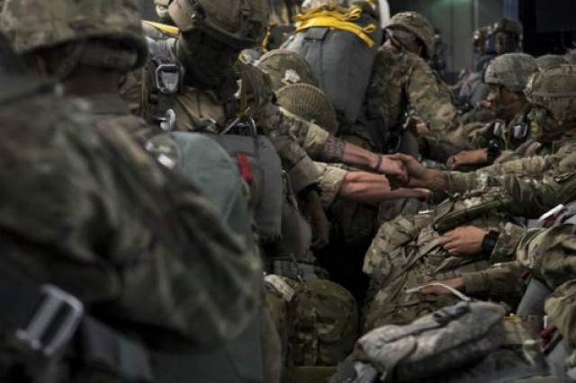 US Army and British Army paratroopers shake hands before jumping from a C-17 Globemaster III over Latvia during Exercise Swift Response 18 June 8, 2018.