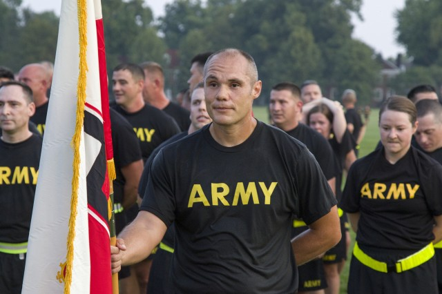 1st Brigade Engineer Battalion, 410th Regiment, 4th Cavalry Multi-Functional Training Brigade observer coach/trainer, Sgt. 1st Class William Waddell, stands at parade rest holding the First Army flag after the Fort Knox Centennial Week run on Aug. 13 at Brooks Field. 1-410th BEB and 4th Cavalry are First Army units. (U.S. Army photo by Sgt. 1st Class Gary J. Cooper)