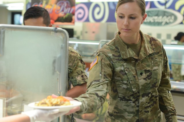 Spc. Mary Calkin, a member of the Washington State National Guard, takes a plate of food at the Freedom Inn Dining Facility at Fort Meade, Maryland. The Army will transition from the old paper meal card system to an automated meal entitlement code system by Oct. 1, 2018.