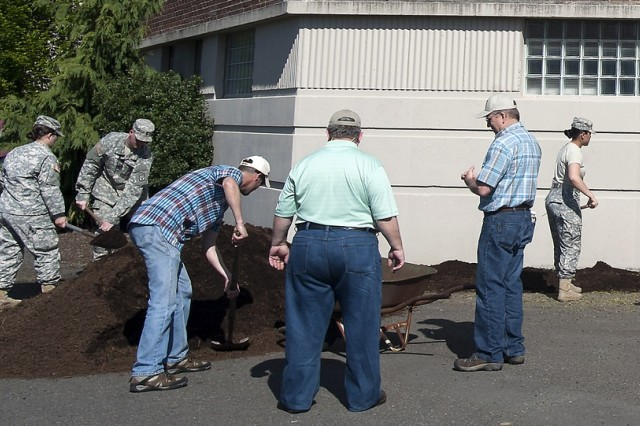 A group of JBLM service members and Directorate of Public Works members join forces to spread beauty bark outside Memorial Stadium on Lewis Main in 2016.