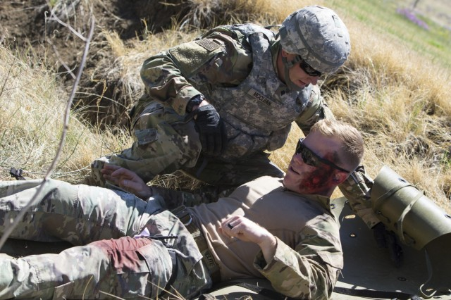 Spc. Michael McClean, an all source intelligence analyst with 71st Ordnance Group (EOD), prepares a simulated casualty, played by 1st Lt. Matt Robertson, for transport during a medical evacuation event of the 71st EOD Soldier/Noncommissioned Officer of the Year competition, May 16, 2018, at the Group's Headquarters.
