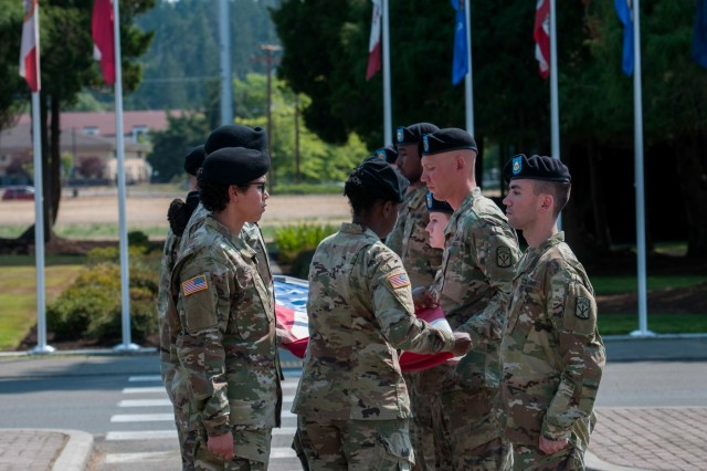 """Flag bears fold the American Flag in front of the I Corps headquarters building during the """"100 years of Courage"""" ceremony held on Joint Base Lewis-McChord, August 9th, 2018.The ceremony was to honor those who served and dedicated themselves over the past 100 years within I Corps. I Corps was activated on January 15th, 1918, in France during World War I, marking a great achievement of 100 years of honor, tradition and courage of units deploying, fighting, winning and innovating in complex wars and missions around the world.To close out the ceremony and the all celebrations for the """"100 years of Courage,"""" a retreat ceremony of the American flag was prepared guided by a speech dedicating each fold to the many sacrifices and duties that the American Soldier performs."""