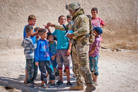 A U.S. Soldier hands out candy to a group of kids during a patrol in their village along the demarcation line outside Manbij, Syria, July 14, 2018. The U.S. and Turkey began conducting independent, coordinated patrols to help reinforce the safety and security in the region after the elimination of ISIS.