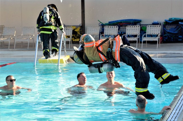 Members of the Joint Base Myer-Henderson Hall Fire Department wait to assist a fully-geared JBM-HH fire-fighting partner upon entry into the water during drown proofing training Friday at Maj. Douglas A. Zembiec Pool.