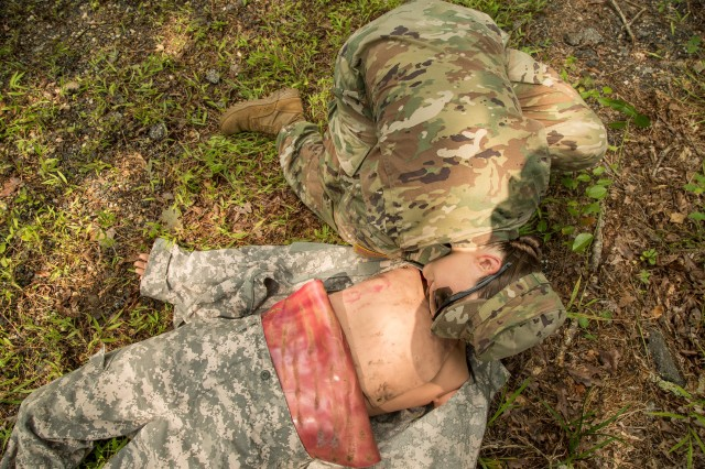 Staff Sergeant Melanie Wahl, assigned to the 704th Military Intelligence Brigade, assesses a simulated casualty during the 2018 Army Cyber Command Best Warrior Competition on Fort Belvoir, Virginia. August 13, 2018. The competition is a battalion-level contest that evaluates Soldiers' physical and mental abilities.