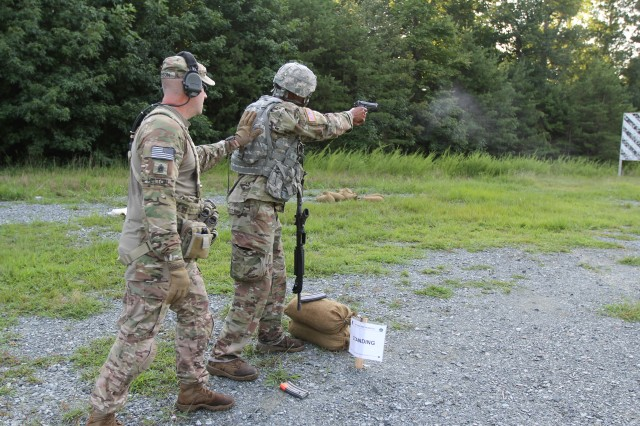 Sgt. 1st Class Deon Myers of the 21st Signal Brigade (right) fires his pistol during a stress shoot on day four of the U.S. Army Cyber Command Best Warrior Competition a, at Camp Upshur on Marine Corps Base Quantico, Virginia, Aug. 15, 2018.