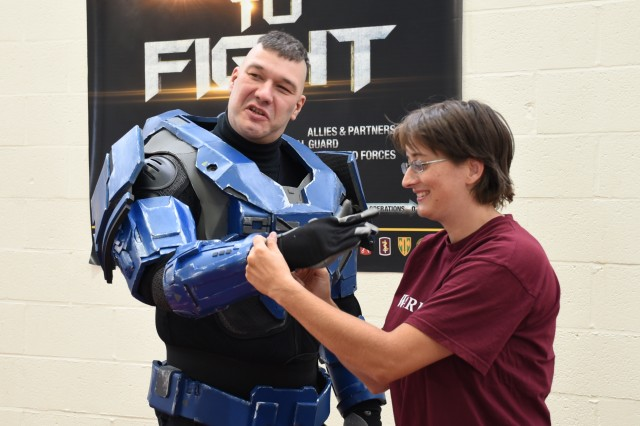 "In preparation for the upcoming SHAPE Geek Convention, Baptistine Smets (right), of Cosplay Corner, gets a gentleman into his Halo character's outfit during the Benelux Welcome Expo Aug. 11, 2018, on Chièvres Air Base, Belgium. The welcome event was a ""one-stop"" shop for community members to get information on services available within the garrison and SHAPE."