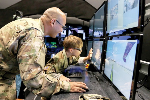 Army Chief Warrant Officer 3 Saul Mulholland, 3rd Assault Helicopter Battalion, 4th Aviation Regiment, shows Carson Raulerson how flight instructors can control environmental variables for pilots training on the Black Hawk simulator at Fort Carson, Colo.