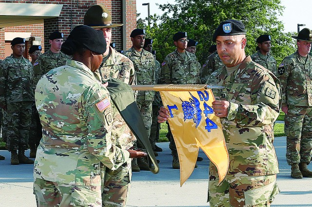 Capt. Jose Ramirez, with the help of 1st Sgt. La'Tangie Dumas (wearing beret) and Sgt. 1st Class John Doody (wearing campaign hat), unfurls the Lima Company guidon during the unit's reactivation ceremony Aug. 15 outside the company headquarters. Ramirez and Dumas make up Lima's leadership team. The company was deactivated April 25, 2016.
