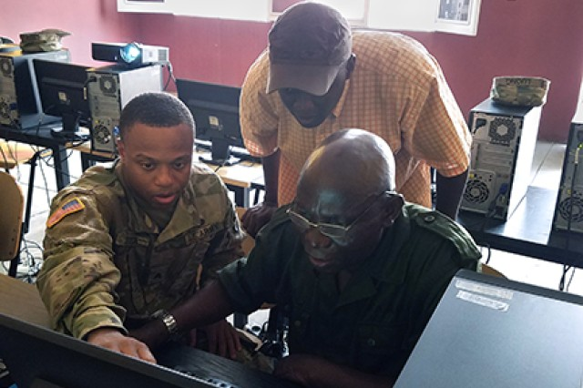 Sgt. Fredrick Stone assists Capt. Nkie Mboranda with lesson planning at the Democratic Republic of the Congo National Logistics School's computer lab on June 22, 2017.