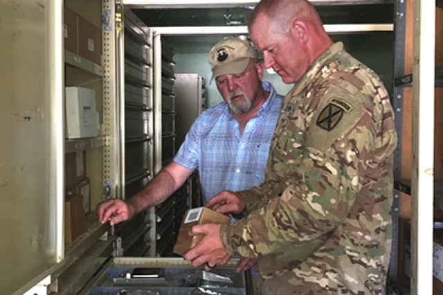 Chief Warrant Officer 2 Michael Beeman, the 210th Brigade Support Battalion maintenance technician, shows Thomas Franzeen, a brigade logistics support team logistics management specialist, how his shop stock is organized to maintain equipment readiness during a Joint Readiness Training Center rotation at Fort Polk, La., on June 14, 2018.