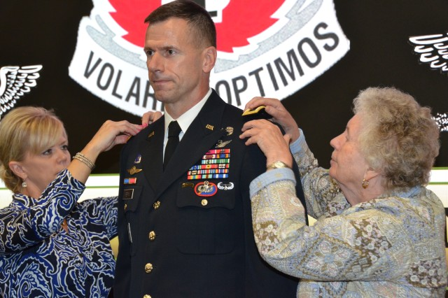 Heather Pepin, wife of Brig. Gen. Allan Pepin, commander, U.S. Army Special Operations Aviation Command, and Pepin's mother, Mary, affixes brigadier general rank on to Pepin's uniform during his promotion ceremony at Fort Bragg, North Carolina, August 20. (Photo by Master Sgt. Shannon Blackwell, USASOAC Public Affairs)