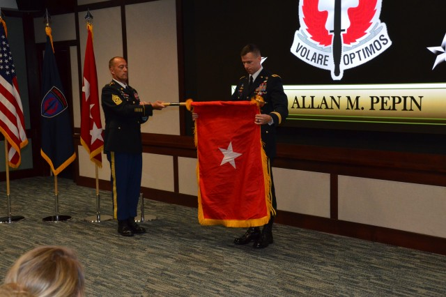Brig. Gen. Allan M. Pepin, commanding general, U.S. Army Special Operations Aviation Command, unfurls his one-star flag with Command Sgt. Maj. Billy D. Webb, USASOAC command sergeant major, during Pepin's promotion ceremony at Fort Bragg, North Carolina, Aug. 20. (Photo by Master Sgt. Shannon Blackwell, USASOAC Public Affairs)