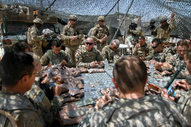 Lt. Gen. Timothy J. Kadavy (center), Director of the Army National Guard, joins the 112th Infantry Battalion, 56th Stryker Brigade Combat Team, 28th Infantry Division, Pennsylvania Army National Guard for a Meal Ready to Eat lunch in the field at the National Training Center, Fort Irwin, California Aug. 16. During their lunch, Kadavy discussed the importance of professional military education, leader development and having strong mentors within units.
