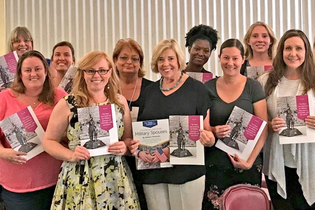 Anne Marshall, Employment Readiness Program Manager, and Kathryn Troutman and 17 military spouses are holding Kathryn Troutman's 'The Stars Are Lined Up for Military Spouses' book after the presentation, learning about military spouse hiring preference into the federal government.
