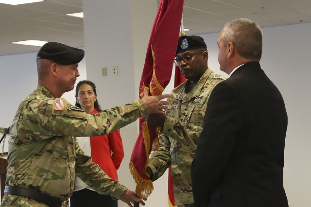 Maj. Gen. Daniel G. Mitchell, left, passes the Watervliet Arsenal colors to Col. Milton G. Kelly, center, during Col. Kelly's assumption of command ceremony on August 21, 2018. Also in photo, Deputy Commander Mr. Joseph P. Turcotte, right, and ceremony narator Ms. Karen Heiser.