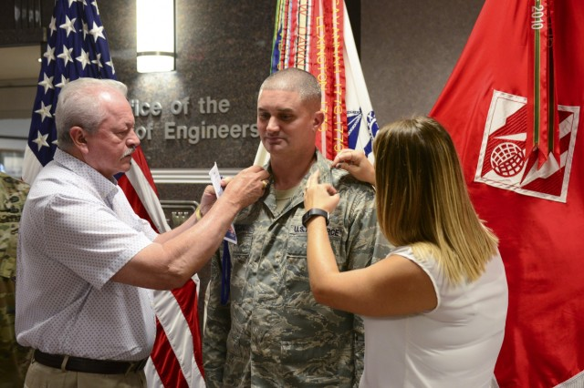 "(Then) Air Force Capt. James ""J.D."" Melton, weather officer, U.S. Army Corps of Engineers is pinned with Major rank by his wife Brittany Melton father James C. Melton at a ceremony at the U.S. Army Corps of Engineers Headquarters in Washington, D.C., August 15, 2018. During the ceremony the senior Melton was formally presented with the Bronze Star Medal he earned for his actions in Vietnam in 1969. (Photo by Jarrell Dillard, U.S. Army Corps of Engineers)"
