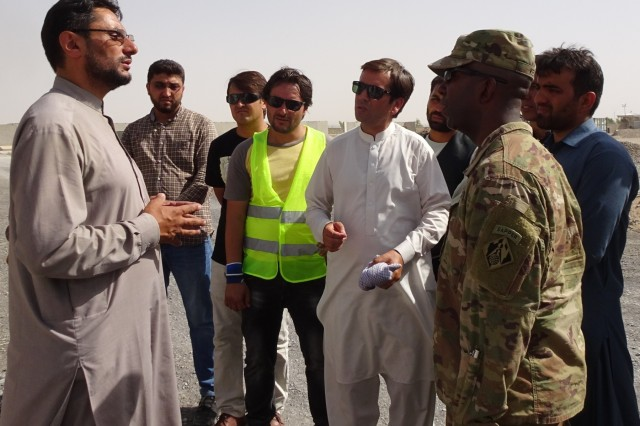 Afghan Technical Support Team member briefs Col. Jason Kelly, Afghanistan District Commander on the Special Mission Wing Power Plant at Kandahar Airfield.