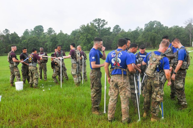 Paratroopers assigned to the 1st Battalion, 319th Airborne Field Artillery Regiment, left, and the 82nd Brigade Support Battalion, right, 3rd Brigade Combat Team, 82nd Airborne Division assemble a cube from PVC piping during a cognitive testing station provided by the Fort Bragg R2 Performance Center during the brigade's August Best Squad Competition conducted August 21 on Fort Bragg.
